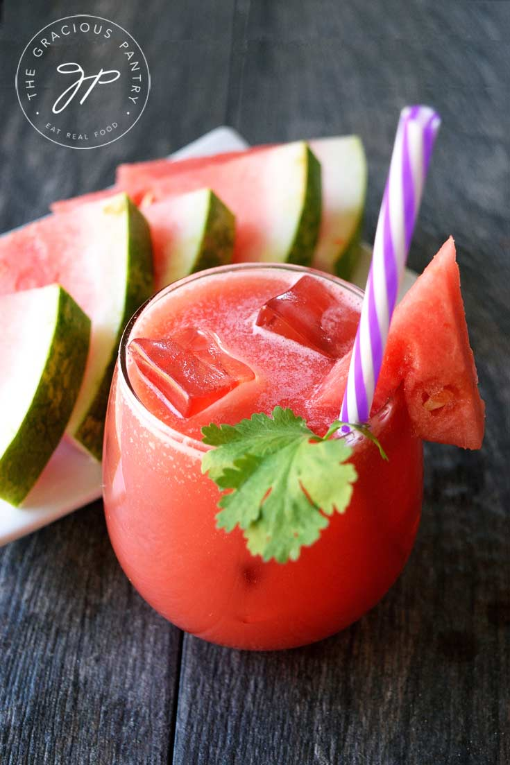 A glass of this Clean Eating Watermelon Lemonade sits next to a plate of watermelon triangles. The glass has ice in it as well as a purple-striped straw and a spring of fresh cilantro.