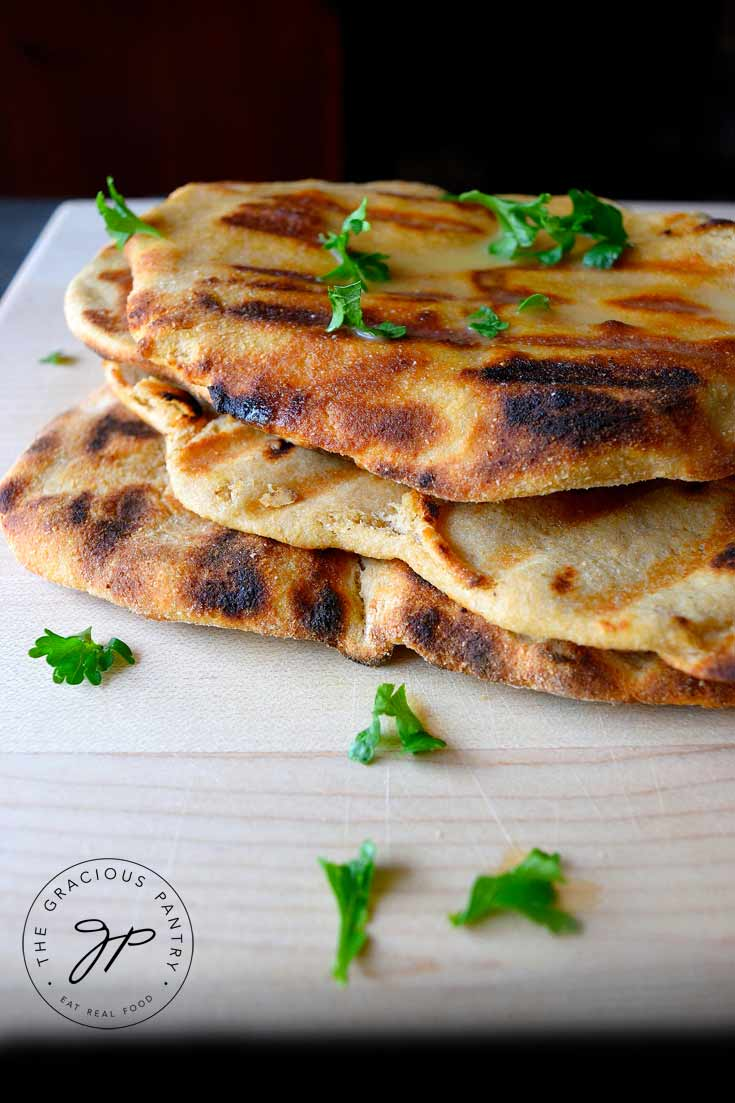 A short stack of four, Clean Eating Grilled Garlic Flatbread sitting on a cutting board. It has melted butter on the top flatbread and there is a little bit of fresh parsley sprinkled over the top.