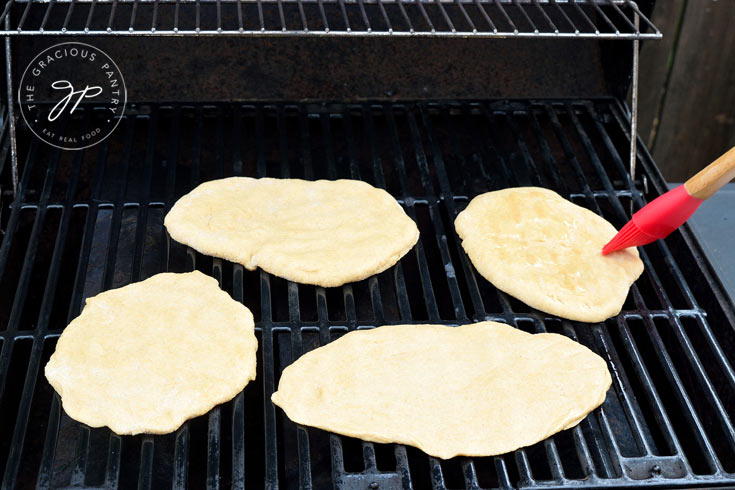 Four, Clean Eating Grilled Garlic Flatbread are cooking on the barbecue.