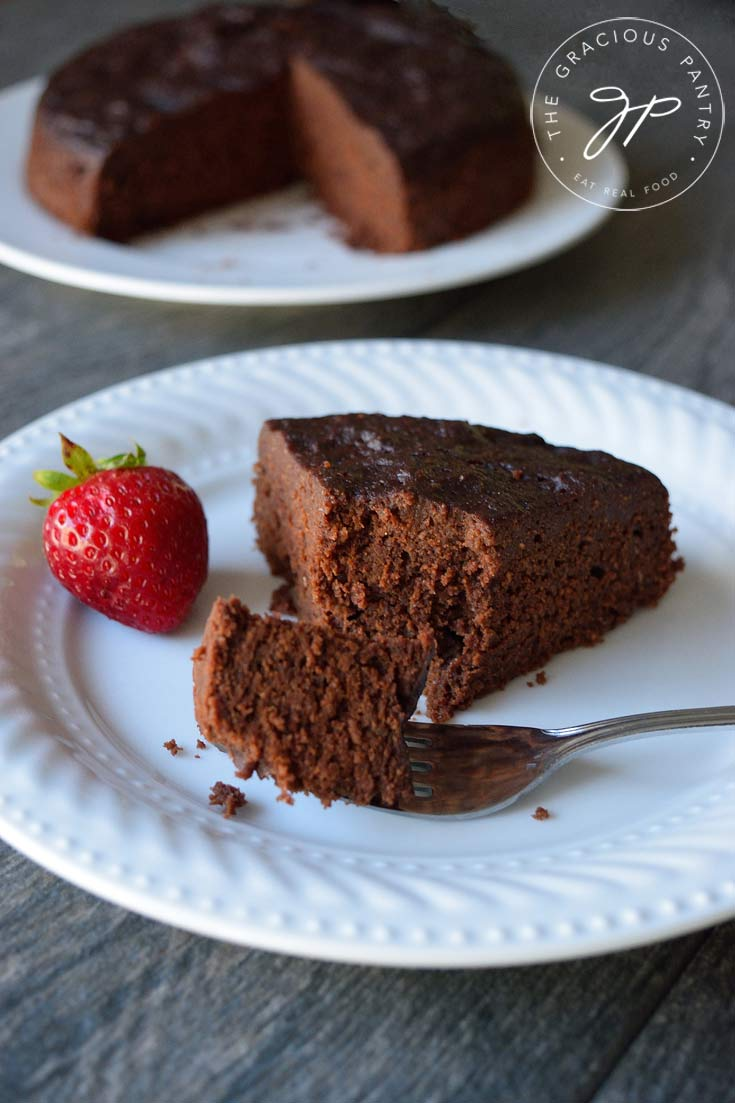 A single slice of this Clean Eating Instant Pot Chocolate Cake sits on a white plate with the rest of the cake in the background.