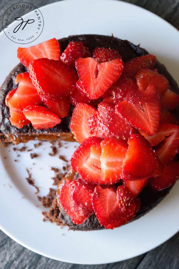 A view of this Clean Eating Instant Pot Chocolate Cake from the top down shows one slice removed and some of the fruit spread filling in the center. The cake is topped with sliced strawberries.