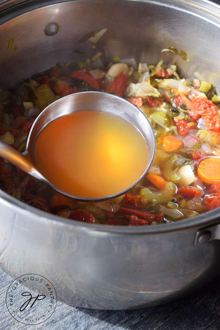 Showing this Clean Eating Vegetable Stock after it's just been made. The veggies and stock are still in the pot and ladle rests in the pot filled with golden-brown vegetable stock.
