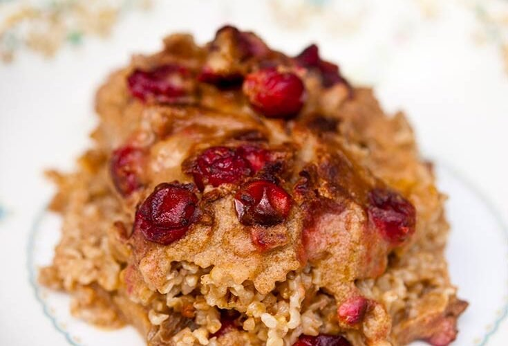 A bowl sits on a dark background with a single serving of this Baked Oatmeal with Pumpkin and Cranberries. There are bright, red, baked cranberries all over the top of the oats.