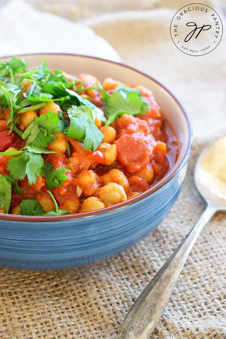 A single bowl of this Clean Eating Mexican Chickpea Stew sits ready to eat, garnished with fresh cilantro sprigs. You can see the red tomato sauce and chickpeas covering the bed of rice underneath.