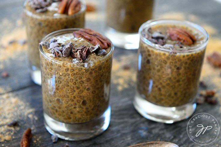 A horizontal shot showing four shooter glasses filled with this Clean Eating Maca Chia Seed Pudding.