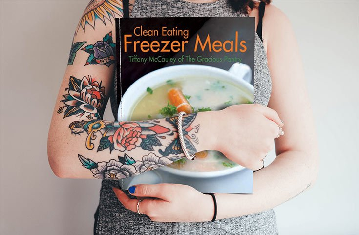 A woman holding the clean eating freezer meals, cradled in her arms at her chest.