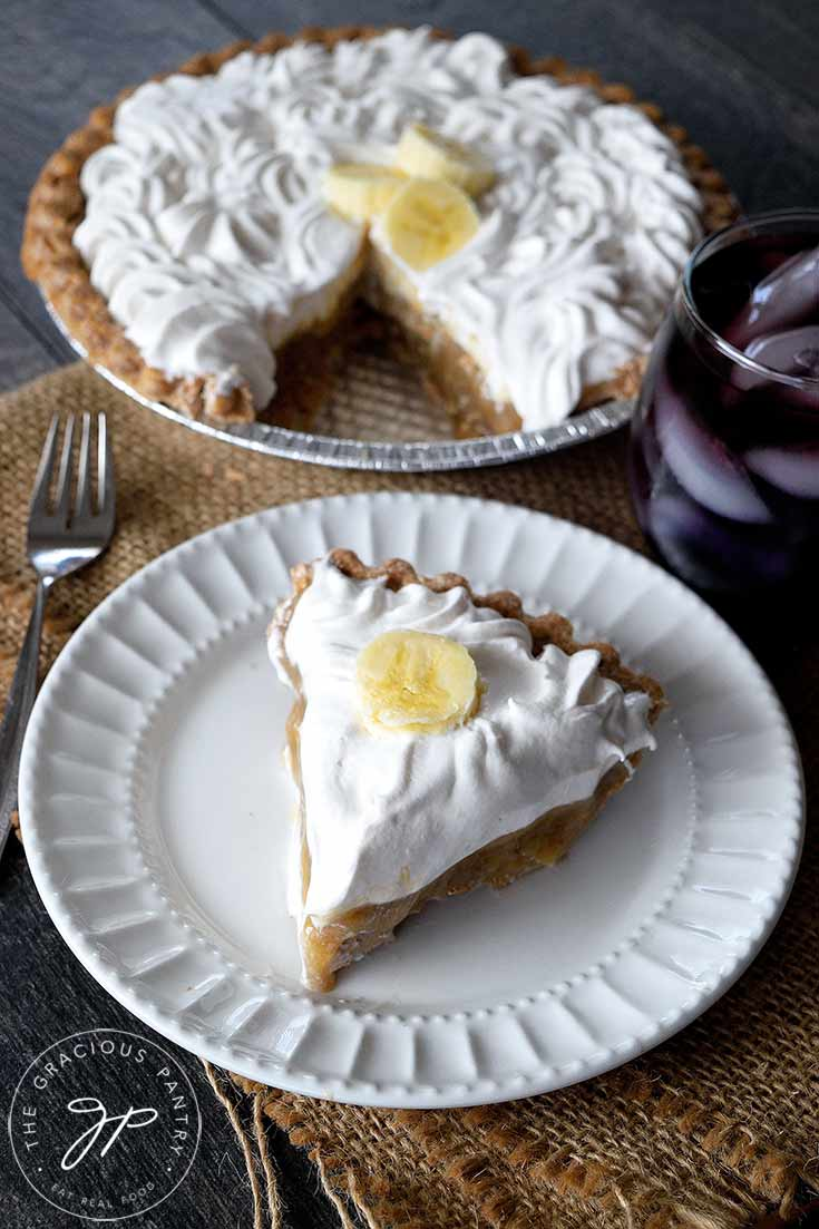 The cut, clean eating banana cream pie is sitting in the background while a white plate with a single slice of pie sits to the front.