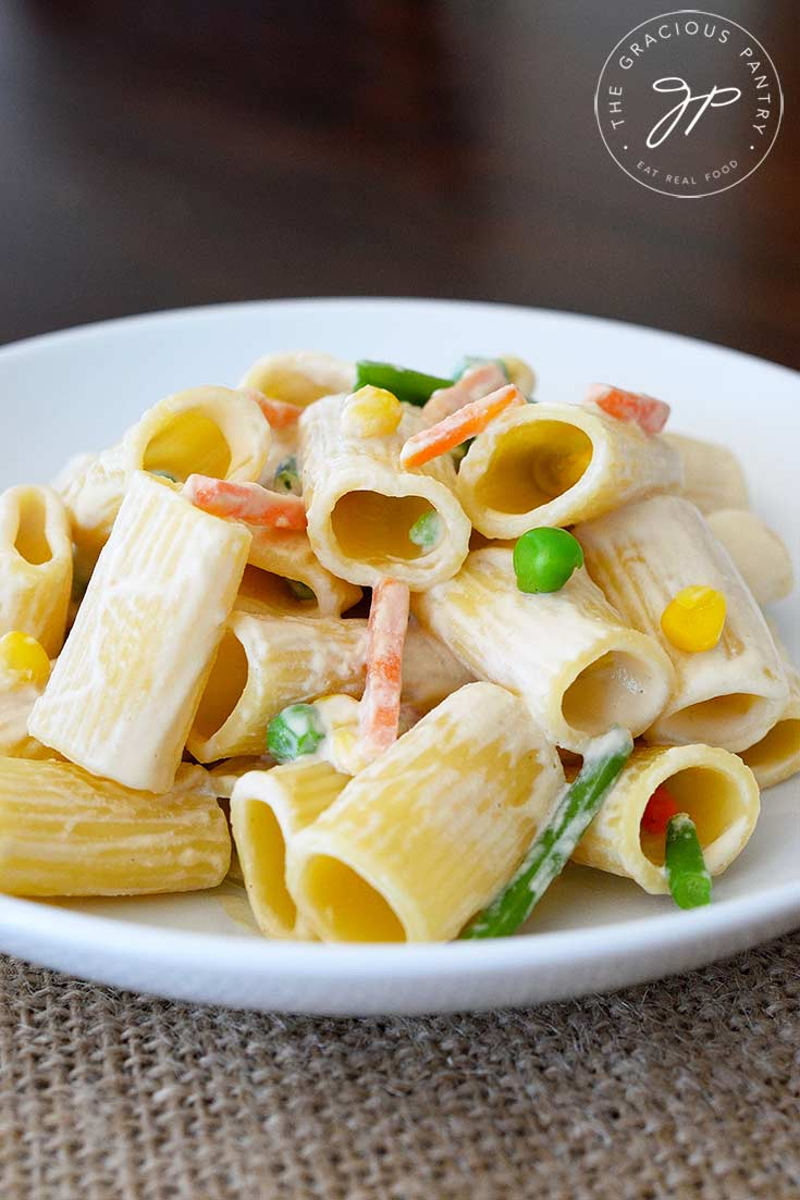 A side view of this dish shows the pasta in a white bowl. You can see into the round rigatoni noodles from the side. There are bits of the mixed veggies in with the sauce that is coating the noodles.