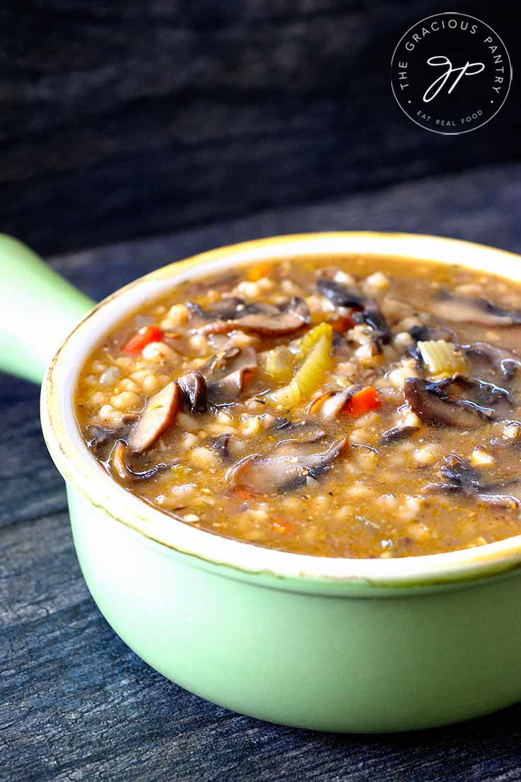 An up close shot of this mushroom barley soup shows the soup in a green bowl with a handle. You can see bits of the carrots and celery along with quite a few mushroom slices.