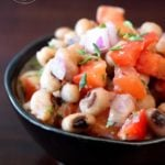 This clean eating black eyed pea salad recipe is displayed in a small, round, black bowl. You can see the beans, tomatoes, peppers and fresh herbs.