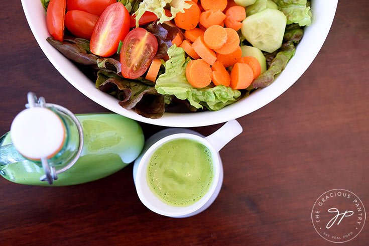 And overhead view looking down into the bowl of salad with carrots, tomatoes and cucumbers. A clear glass bottle and small white pitcher both sit in front of the bowl filled with this clean eating green goddess dressing recipe.