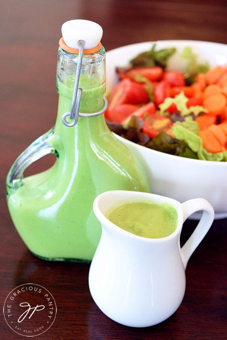 A beautiful bowl of salad sits towards the back of the table with a full dressing bottle and a small, white pitcher sit filled with this clean eating green goddess dressing recipe.