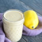 A single jar of this clean eating lemon tahini dressing recipe sits on a gray surface with a purple towel at it's base and a lemon to the right.