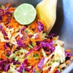 This fresh, clean eating Mexican coleslaw recipe is being served in a silver, metalic bowl. It has a half of a lime wedged in at the side of the bowl and a wooden serving spoon sits nested at the side of the bowl as well.