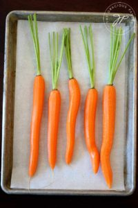 A tray of carrots sits ready to be dressed for roasting in this clean eating maple glazed carrots recipe.