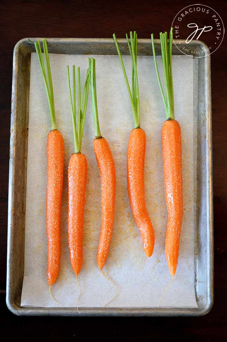 A tray of carrots sits ready for roasting in this clean eating maple glazed carrots recipe.