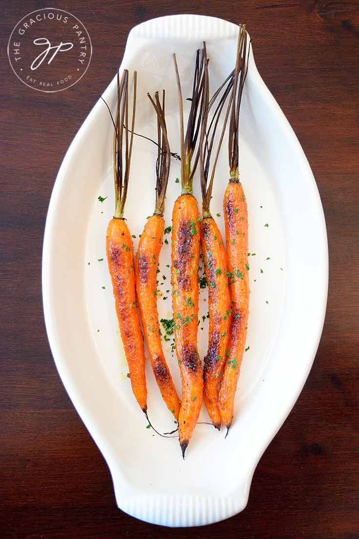 An overhead look at these clean eating maple glazed carrots. They sit in an off white, oval serving dish.