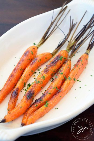 A side view of these clean eating maple glazed carrots shown in an oval serving dish.