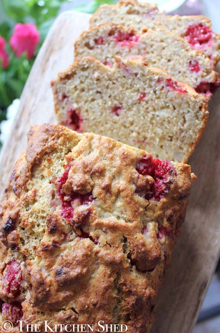 A few slices are cut and laying next to this loaf of Clean Eating Raspberry Vanilla Banana Bread.