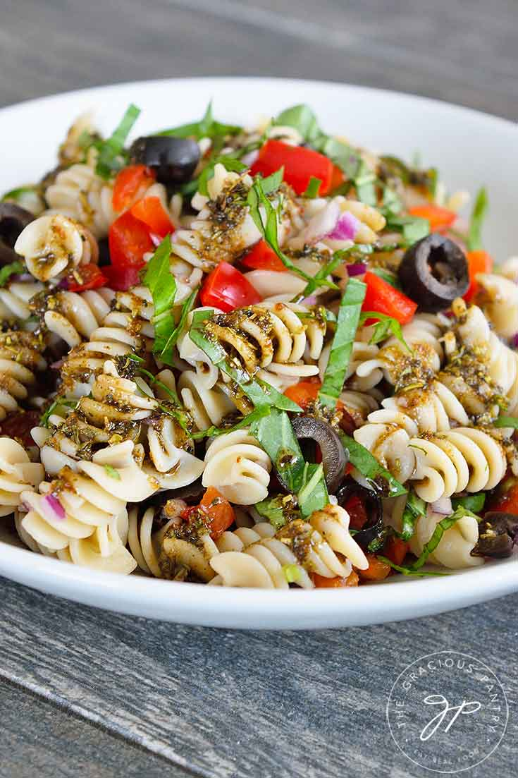 A side view of this Clean Eating Rustic Italian Pasta Salad Recipe shows the pasta, red peppers and fresh basil in a white bowl.