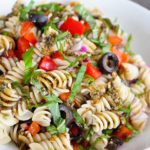 A white bowl sits filled with this Clean Eating Rustic Italian Pasta Salad Recipe. You can see bits of olives, red peppers, fresh basil and a bit of the dressing scattered throughout the pasta.