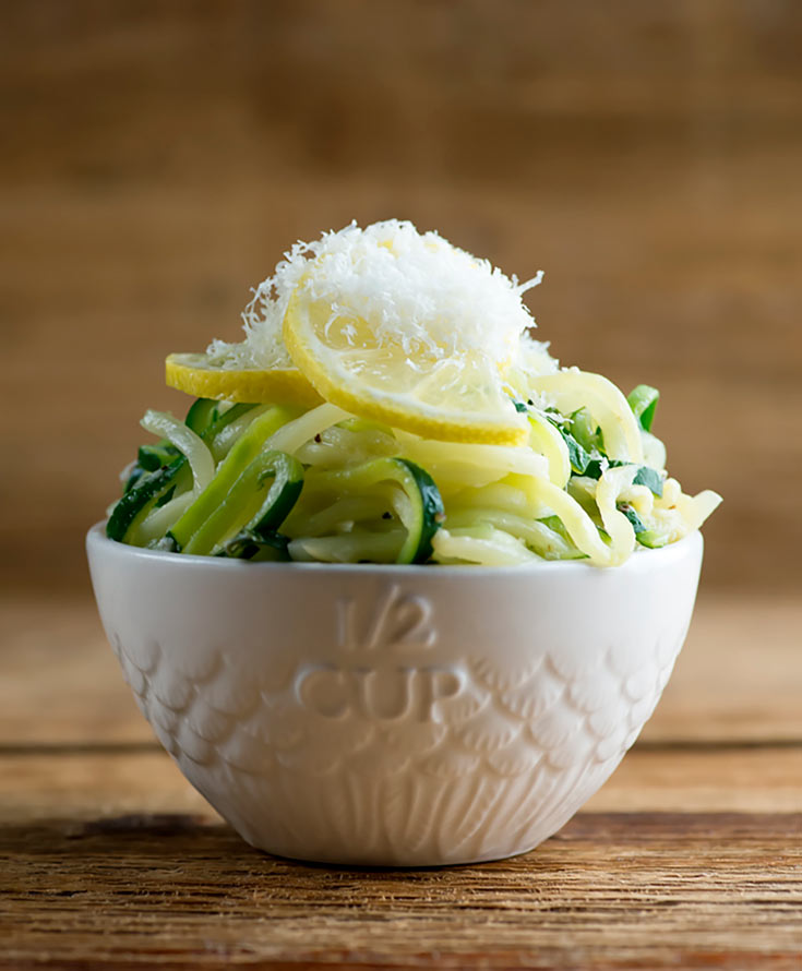 A white bowl sits filled with this Clean Eating Lemon Parmesan Zucchini Noodles on a wooden table. A lemon slice sits on top of the zucchini noodles and everything is topped with freshly grated parmesan cheese.