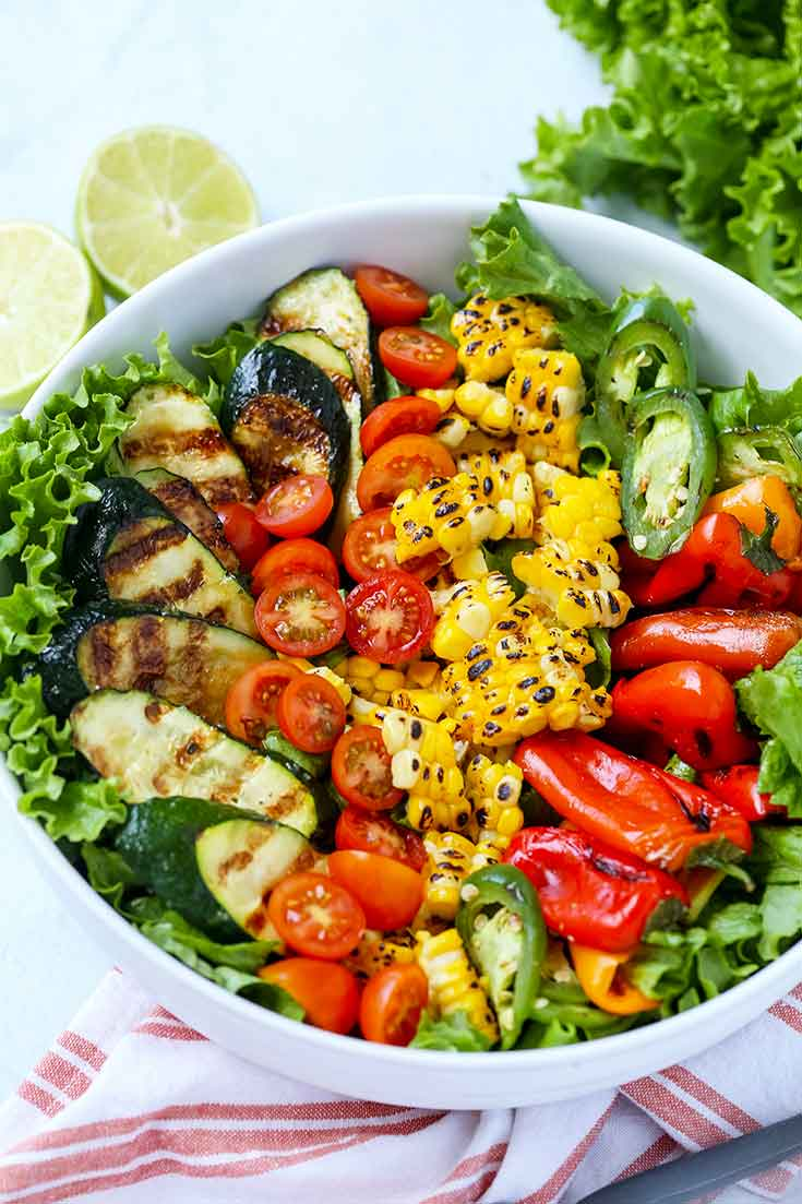 A white bowl containing this Clean Eating Grilled Garden Salad looks vibrant with grilled corn, peppers, zucchini and some fresh cherry tomatoes in a bed of salad greens.
