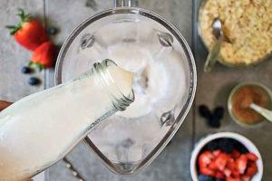 Adding almond milk to the blender.