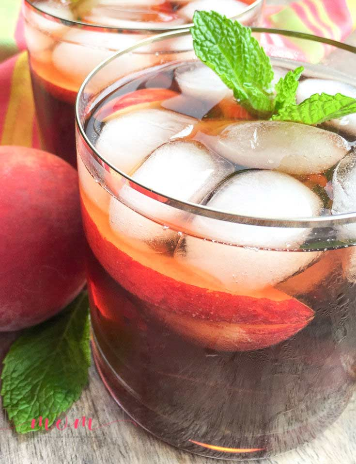 A side view of this clean eating peach iced tea recipe shows the tea in a clear glass with ice cubes and a sprig of fresh mint at the top of the glass.