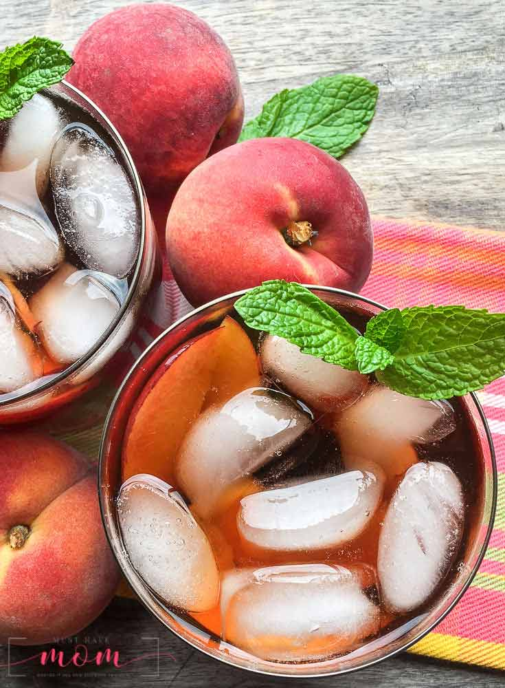 An overhead view of this clean eating peach iced tea recipe shows two glasses sitting on a table next to a peach, filled with the dark brown tea, ice cubes and some fresh mint.