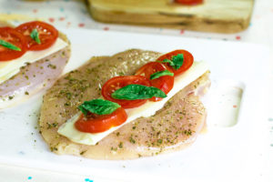The next step in this Air Fryer Chicken Breasts Recipe is to layer the cheese, tomatoes and fresh basil onto the butterlied chicken breasts.