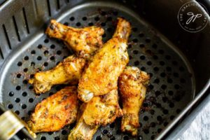 Step 6 shows the cooked wings sitting in the air basket after just finishing cooking.