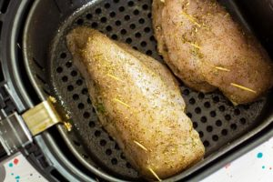 To cook this Air Fryer Chicken Breasts Recipe, place the prepared chicken breast into the air fryer basket.