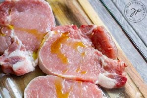 Pork chops on a cutting board, drizzled with a small amount of oil.