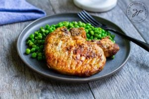 Air fried pork chops on a plate with a side of green peas.