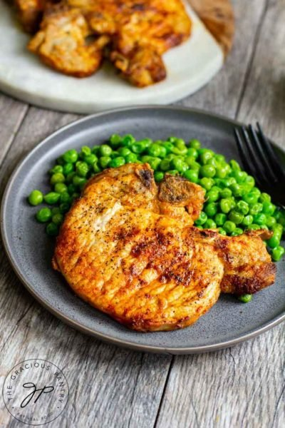 A plate of air fried pork chops sits next to a side of peas with left over pork chops sitting on a board to the side.