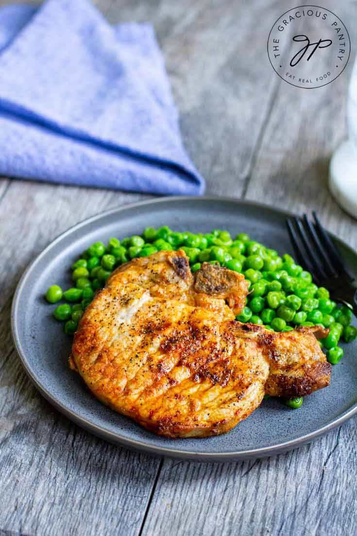 A plate of air fryer pork chops with a side of peas sits on the table next to a blue napkin,