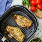 This chicken from this Air Fryer Chicken Breast Recipe still sits in the air fryer basket after just finishing the cooking cycle. Two cooked breasts sit in the basket, ready to serve.