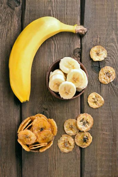 A single, whole banana lays on a wooden table top with a dish of sliced bananas next to it as well as dried banana chips strewn about.