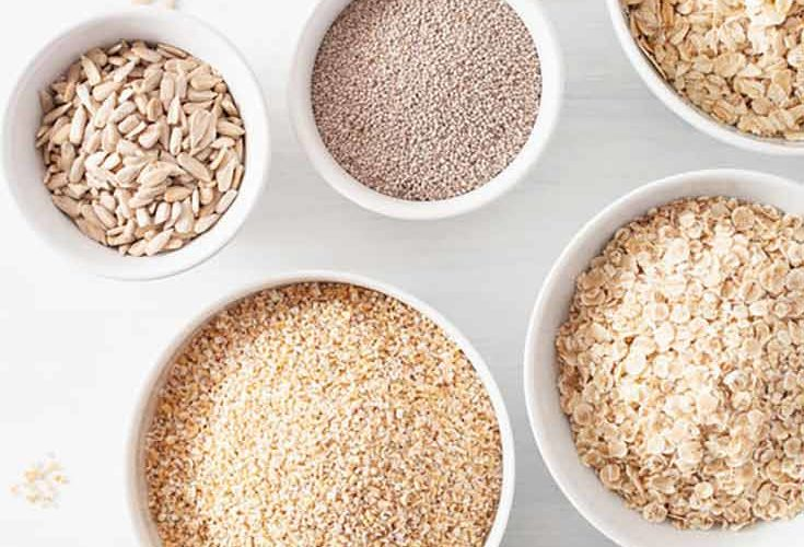 Bowls of different types of oats and oatmeal toppings sit on a white background in this guide for how to make oatmeal