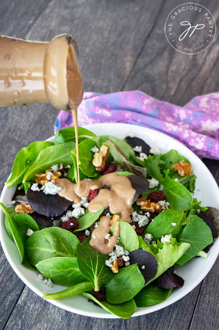 A beautiful bowl of cranberry walnut salad sits on a table and this blue cheese vinaigrette is being poured over the top.