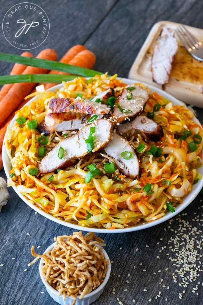 This Chinese Chicken Salad sits surrounded by carrots, green onions, ramen noodles and a small cutting board with a fork where the chicken was sliced.