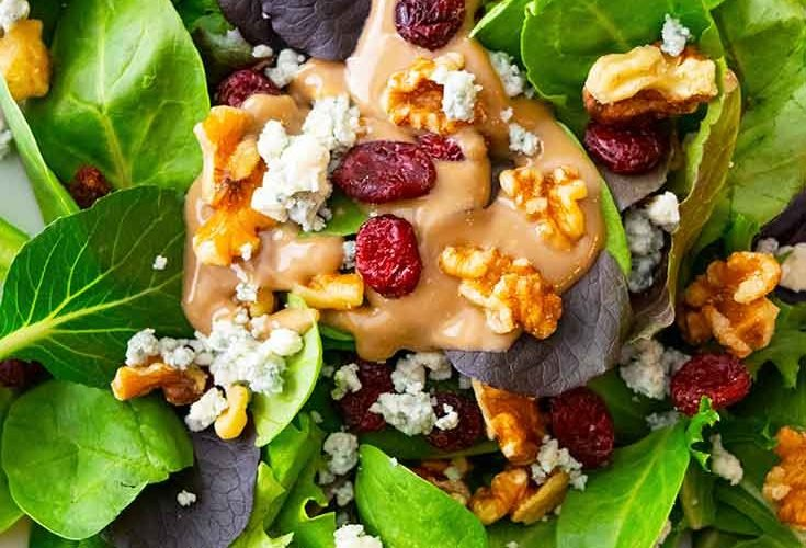 An overhead view looking down into a white bowl filled with this Cranberry Walnut Salad.