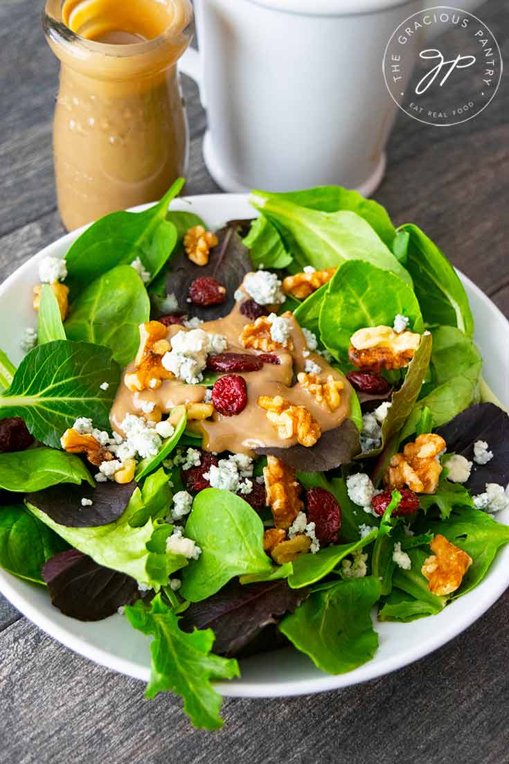 A bowl of this Cranberry Walnut Salad sits next to a jar and mixing pitcher of the blue cheese vinaigrette I used on this salad.
