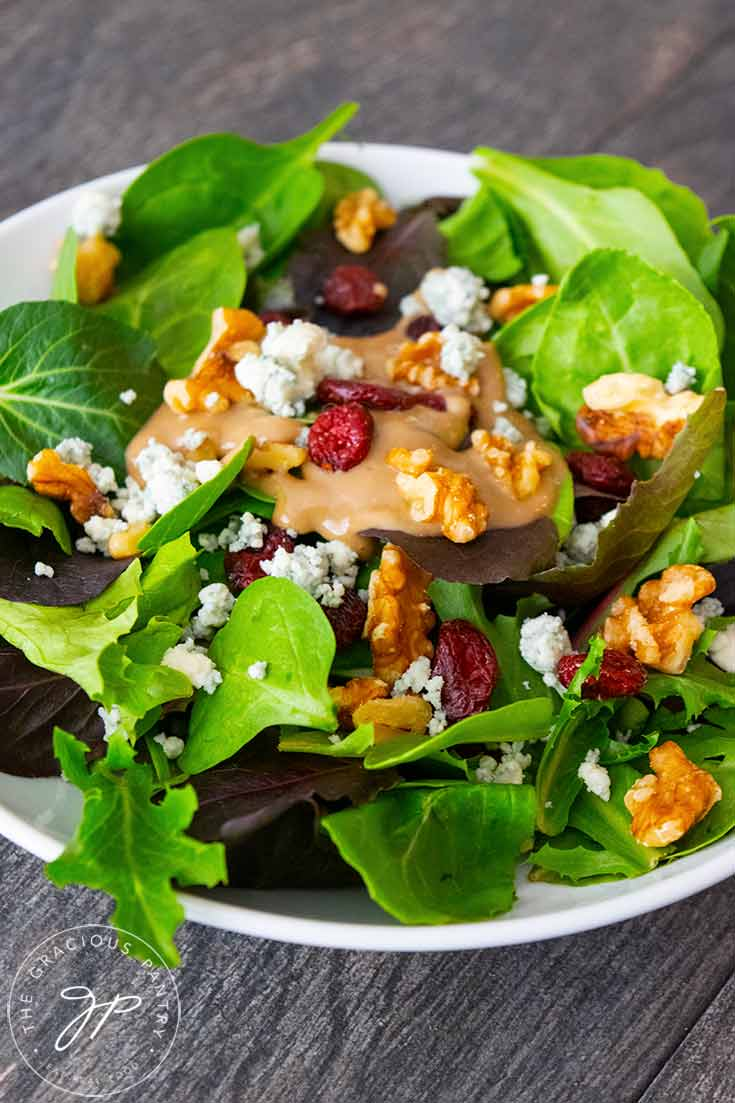 A side view of this Cranberry Walnut Salad shows the varied lettuces in the spring mix, the bright red cranberries and golden brown walnuts with sprinkles of blue cheese crumbles.
