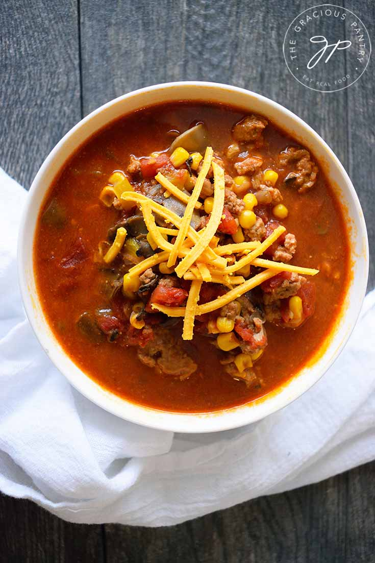 And overhead view of this Instant Pot Turkey Chili in a white bowl. You can see bits of turkey and corn and tomatoes with shredded cheddar sprinkled over the top.