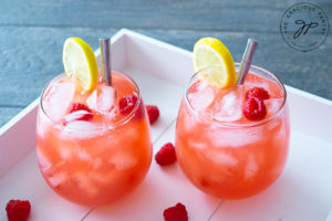 Two glasses filled with raspberry lemonade sit on a white serving tray, ready to serve.