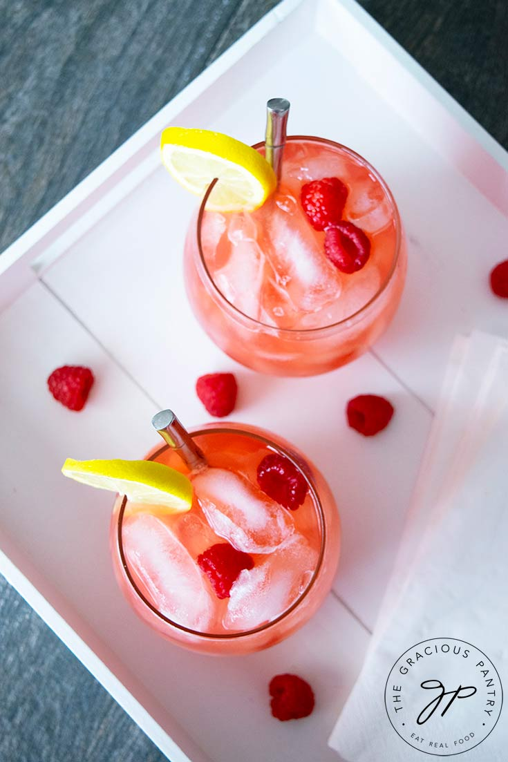 And overhead view of two glasses of raspberry lemonade sitting in a white serving tray.