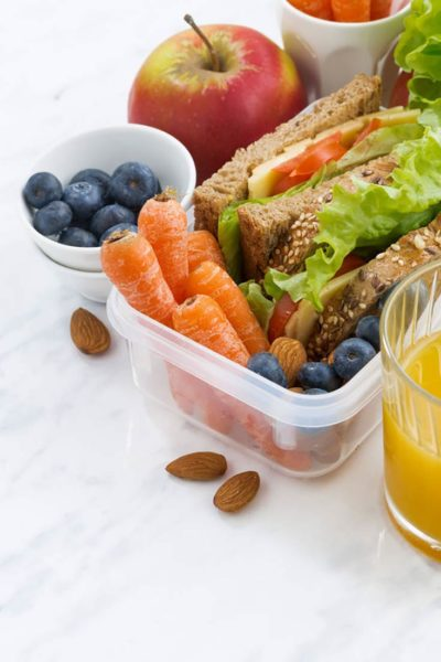 A healthy school lunch sits ready to eat. There are blueberries, carrots, an apple and a whole grain sandwich in lunch containers.