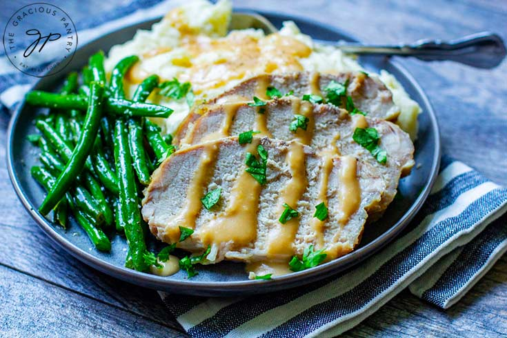 The last step of this Slow Cooker Pork Loin Recipe shows the pork sliced and sitting on a plate next to mashed potatoes and green beans, with gravy drizzled over the top of the meat and potatoes.